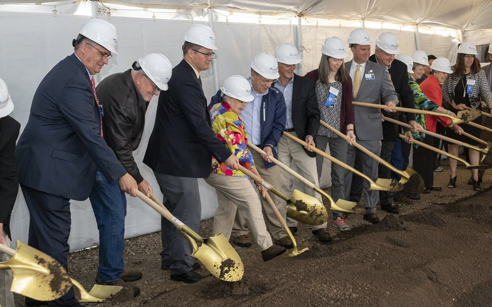 The ground breakers lift their shovels from the pile of dirt