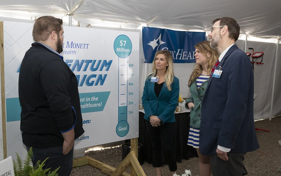 CoxHealth employees review the Momentum Campaign poster