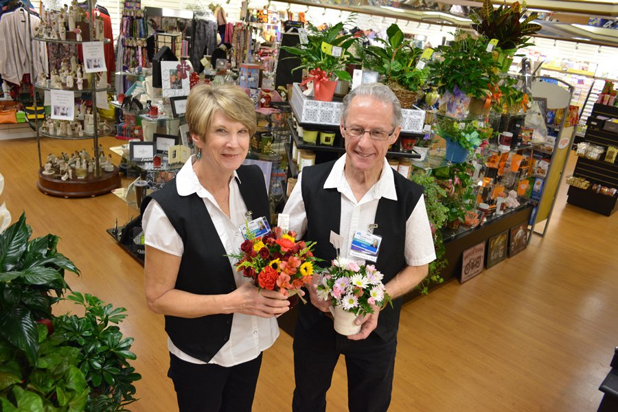 Two CoxHealth gift shop employees smile and hold gifts.