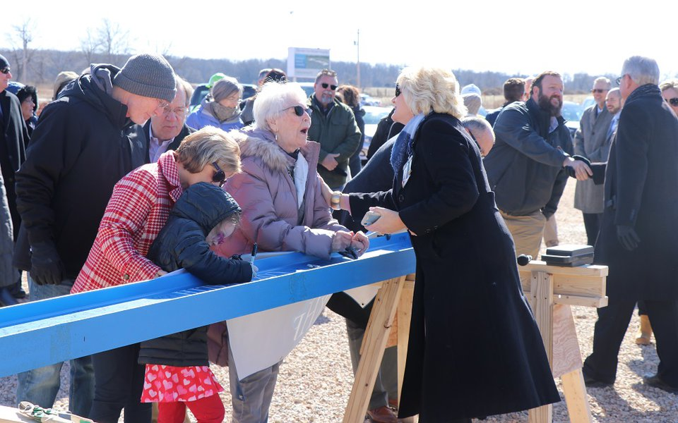 The community signing the last beam to go up on the structure of the new Cox Monett Hospital