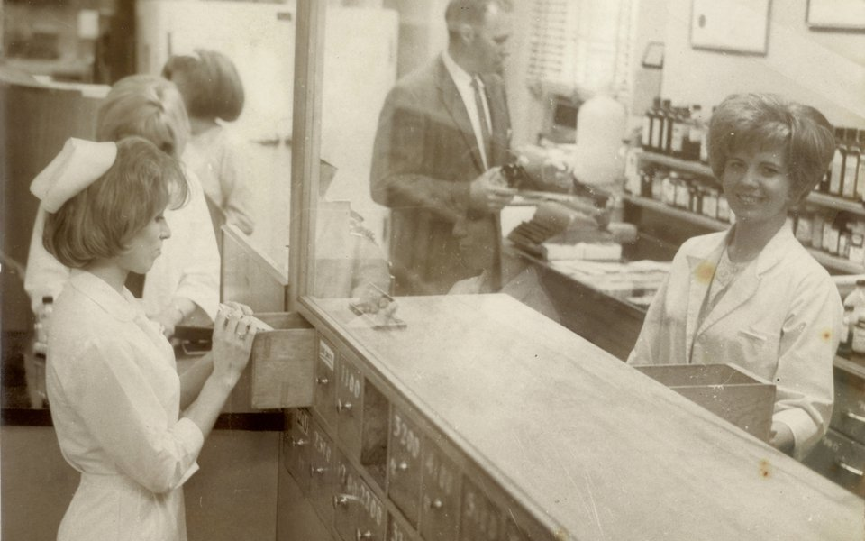 A nurse smiles at the camera at a CoxHealth pharmacy in the late early 60s