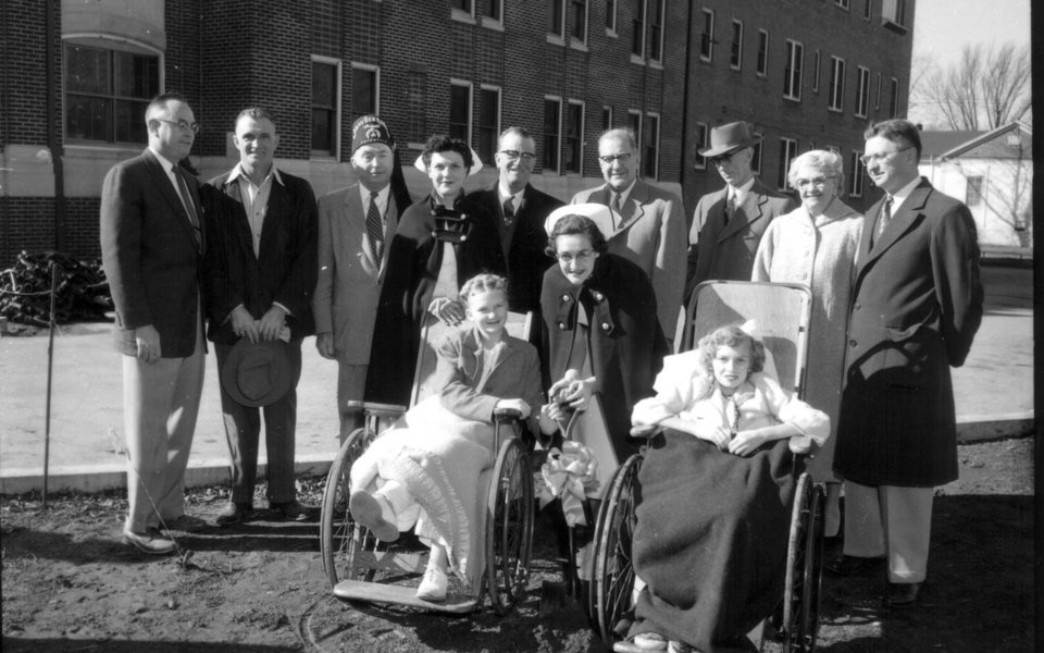 A historic photo of a group of people standing around polio patients in wheelchairs at CoxHealth